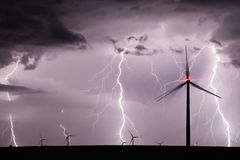 Thunderstorm over a wind farm representing renewable energy. Night thunderstorm with powerful lightnings over a wind farm Stock Photography