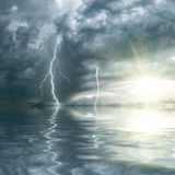 Thunderstorm with rain and lightning. Over ocean, the sun shines through clouds Royalty Free Stock Photography