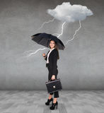 Thunderstorm strikes to businesswoman. With umbrella in the gray room Royalty Free Stock Images