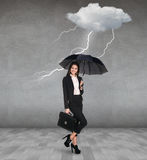 Thunderstorm strikes to businesswoman. With umbrella in the gray room Royalty Free Stock Image