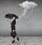 Thunderstorm strikes to businesswoman. With umbrella in the gray room Stock Photography
