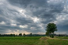 Thunderstorm with sunrays shining through altocumulus asperitas clouds over the countryside near Wuustwezel Belgium, close to th royalty free stock photo