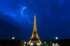 Thunderstorms behind Eiffel Tower at night Stock Images