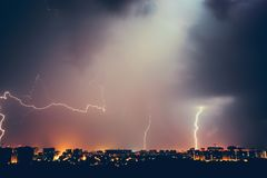 Thunderstorms vivid dramatic cloudy sky and lightnings above night city. Toned royalty free stock image