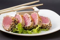 Thunfischleiste auf weißem Teller mit Salat und Sojasoße stockbilder