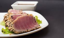 Thunfischleiste auf weißem Teller mit Salat und Sojasoße Stockfoto