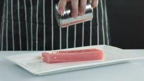 Thunfischleisten werden mit Samen des indischen Sesams besprüht stock video