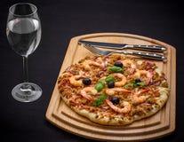 Thunfischpizza mit Garnele und Wasser, Tischbesteck Stockfotos