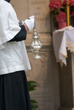 Thurible held by altar boy. Catholic thurible burning incense at mass Stock Photo