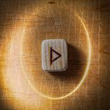 Thurisaz. Handmade scandinavian wooden runes on a wooden vintage background in a circle of light. Concept of fortune stock photography