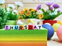 Thursday. Colorful cube letters on sticky note block. Thursday. Colorful cube letters on sticky note block and wooden pallets as a background royalty free stock photos