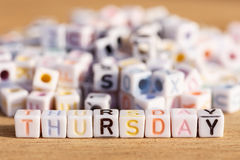 Thursday written in letter beads on wood background Stock Photos