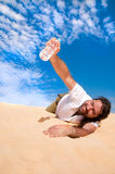 Thursty man got water. Thirsty man in the desert with a bottle of water stock photo
