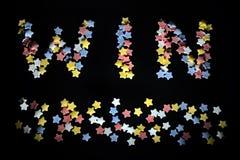 Thw słowa wygrana w czerwonych białych koloru żółtego i błękita cukrowych gwiazdach dla biznesu, trenowanie, sportów fan, sukces, fotografia stock