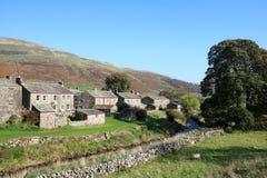 Thwaite beck och by Swaledale North Yorkshire royaltyfria bilder