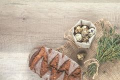 Thyme branch, quail eggs and rye bread. Thyme bunch, quail eggs and rye bread on the wooden background with copy space, toned photo Royalty Free Stock Photos