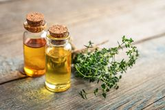 Thyme essential oil. In a glass bottle with cork stopper and fresh thyme herb  on wooden background Royalty Free Stock Photos