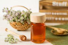 Thyme honey in a jar on a white wooden background. Thyme honey in a jar and fresh herbs on a white wooden background royalty free stock photo
