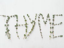 Thyme leaf sprigs forming the word Thyme over white background. Fresh thyme leaf sprigs forming the word Thyme over white background Royalty Free Stock Photos