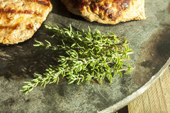 Thyme, near steaks. On a stone plate Royalty Free Stock Image