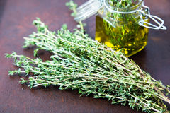 Thyme oil. Thyme essential oil jar glass bottle and branches of. Plant Thyme with flowers on rustic background Royalty Free Stock Images