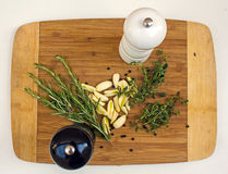 Thyme, rosemary, garlic, salt, pepper on the wooden cutting board. Ready for cook Royalty Free Stock Photos