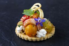 Elegant tart with crayfish. Thyme tart with crayfish, goat cheese mousse, fennel, tomatoes and crispy potato royalty free stock image