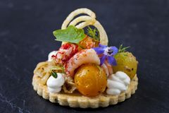 Elegant tart with crayfish. Thyme tart with crayfish, goat cheese mousse, fennel, tomatoes and crispy potato stock images