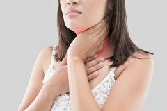 Thyroid gland. Asian woman with sore throat or neck pain or thyroid gland against gray background. People body problem concept royalty free stock images