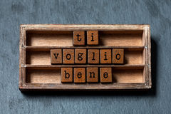 Ti voglio bene. I love you written in Italian translation. Vintage box, wooden cubes phrase with old style letters. Gray Royalty Free Stock Photography