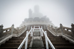 Tian Tan Buddha (den stora Buddha) i dimma, på Ngong knackar, Lantau I Arkivfoton