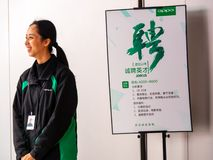 TIANHE, GUANGZHOU CITY, CHINA - 7 MAR 2019 - A smiling Oppo employee stands next to an staff recruitment poster seeking sales stock photos
