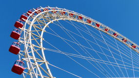 Tianjin eye. Dramatic view from below of a large Ferris wheel, the Tianjin Eye in China, red cabins against a clear blue sky Royalty Free Stock Image