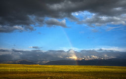 Tianshan Rainbow. After a while pelting rain, a rainbow through the dark clouds falls Tianshan xuefeng before, the United States Meilen calls Royalty Free Stock Photography