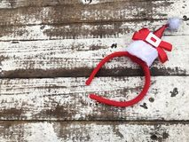 Tiara de la Navidad con el sombrero rojo en un fondo de madera blanco Fotografía de archivo libre de regalías
