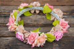 Tiara de rosas artificiales en fondo de madera Imagenes de archivo