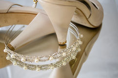Tiara and shoes. A tiara sitting next to a pair of beige shoes Stock Photos
