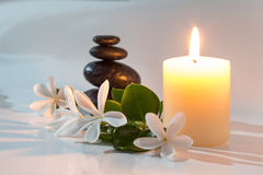 Tiare flowers, candle and black stone spa. Massage - tiare flowers, candle and black stone spa royalty free stock photography