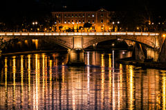 Tiber River, bridge and reflections on water. Night Rome, Italy.