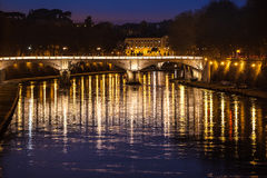 Tiber River, bridge and reflections on water. Night Rome, Italy. Night photography of Rome, Italy. Tiber River, bridge and reflections in the water. Historical Stock Images