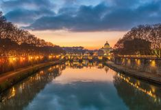 Rome, Italy - The Lungotevere with Tiber river and the Saint Peter basilica in Vatican. The Tiber river and the monumental Lungotevere at sunset and blue hour stock photo