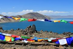 Tibet, Buddhist flags with mantras in front of holy lake Co lake in summer sunny day.  stock photo