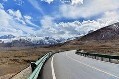 Tibet lång väg framåt med det främsta höga berget Arkivfoto