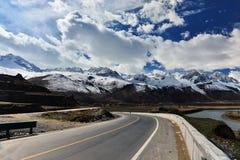 Tibet lång väg framåt med det främsta höga berget Royaltyfri Bild