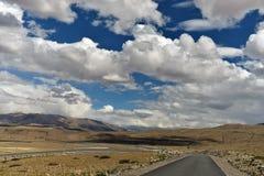 Tibet lång väg framåt med det främsta höga berget Fotografering för Bildbyråer