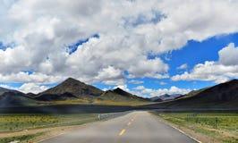 Tibet lång väg framåt med det främsta höga berget Arkivbilder