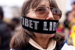 Tibet Libre. A woman wears a banner covering her mouth saying TIBET LIBRE which means FREE TIBET. Demonstration in Paris, France. March 10th, 2012 Stock Photos