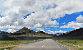Tibet Long way ahead with high mountain in front Stock Images
