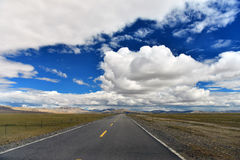 Tibet Long way ahead with high mountain in front Stock Photos