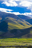 Tibet mountains. High mountains of Tibet covered with grass with clouds in background Royalty Free Stock Photography